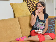 Young Hispanic woman at home. Beautiful young Hispanic woman sitting on couch in her pajamas (sweats) holding a bowl of almonds - healthy snack Stock Photography