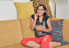 Young Hispanic woman at home. Beautiful young Hispanic woman sitting on couch in her pajamas (sweats) holding a bowl of carrots - healthy snack Royalty Free Stock Photos
