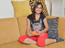Young Hispanic woman at home. Beautiful young Hispanic woman sitting on couch in her pajamas (sweats) holding a bowl of carrots - healthy snack Stock Images