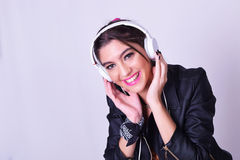 Young hispanic woman listening to music with headphones Stock Images