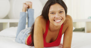 Young Hispanic woman lying on bed smiling Stock Photos