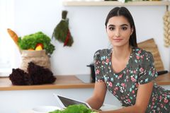 Young hispanic woman is making online shopping by tablet computer and credit card. Housewife found new recipe for Royalty Free Stock Image