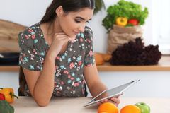 Young hispanic woman is making online shopping by tablet computer and credit card. Housewife found new recipe for Stock Images