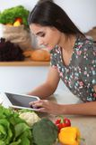Young hispanic woman is making online shopping by tablet computer and credit card. Housewife found new recipe for. Cooking in a kitchen Royalty Free Stock Photography