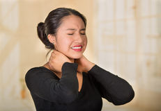 Young hispanic woman posing for camera showing signs of neck pain, holding hands on painful part of body, injury concept Royalty Free Stock Photos