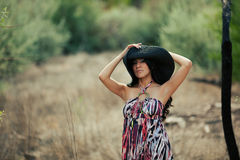 Young Hispanic woman posing with large straw hat. Young Hispanic woman in a field outside, posing with a large straw hat, with a serious expression on her face Royalty Free Stock Images