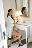 Young Hispanic woman putting on makeup Stock Image