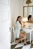 Young Hispanic woman putting on makeup Stock Photos