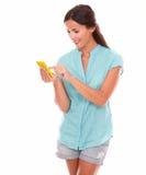 Young hispanic woman sending text message Stock Photo