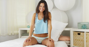 Young Hispanic woman sitting on bed laughing Royalty Free Stock Photos
