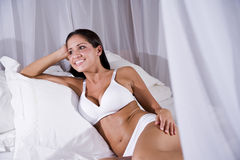 Young Hispanic woman sitting on white canopy bed Stock Photography