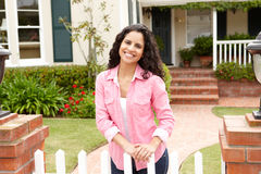 Young Hispanic woman standing outside home. Smiling at camera Stock Image