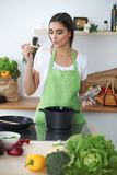 Young hispanic woman or student cooking in kitchen stock photography
