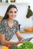 Young hispanic woman or student cooking in kitchen. Girl using tablet to make online shopping or find a new recipe. Stock Images