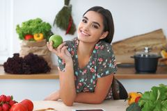 Young hispanic woman or student cooking in kitchen. Girl using tablet to make online shopping or find a new recipe. Young hispanic woman or student cooking in stock images