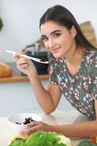 Young hispanic woman or student cooking in kitchen. Girl tasting fresh salad while sitting at the table stock image