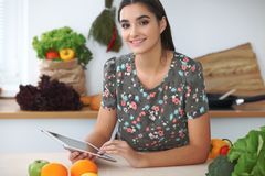 Young hispanic woman or student cooking in kitchen. Girl using tablet to make online shopping or find a new recipe. Young hispanic woman or student cooking in Royalty Free Stock Photo