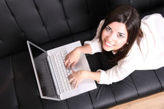 Young Hispanic Woman surfing on the Sofa Royalty Free Stock Photo