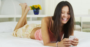 Young Hispanic woman texting on bed Stock Image