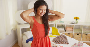 Young Hispanic woman trying on clothes in bedroom Stock Image