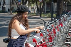 Young hispter lady using the street bikes of the mexican urban program EcoBici. Mexico City Mexico royalty free stock photo