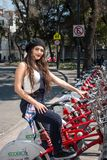 Young hispter lady using the street bikes of the mexican urban program EcoBici. Mexico City Mexico stock image