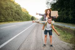 Young hitchhiking couple with empty cardboard. Hitchhike adventure of men and woman. Happy hitchhikers on road Royalty Free Stock Image