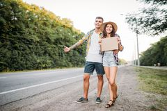 Young hitchhiking couple with empty cardboard. Hitchhike adventure of men and woman. Happy hitchhikers on road Royalty Free Stock Images