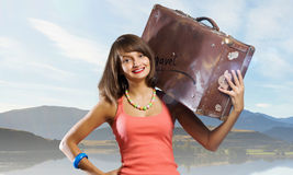 Young hitchhiking traveler. Young pretty girl with her retro suitcase on shoulder Royalty Free Stock Photo