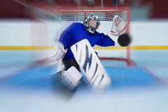 Young hockey goalie catching a flying puck Royalty Free Stock Images
