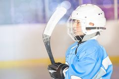 Young hockey player preparing to go out on rink. Side-view portrait of young hockey player in blue uniform, preparing to go out on ice rink stock image