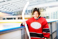 Young hockey player is ready to hit the ice. Portrait of smiling boy, young hockey player in protective equipment, standing next to the rink boards, ready to hit stock photography