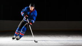 Young hockey player skating on rink in attack Stock Photography