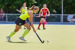 Young hockey player woman with ball in attack. Playing field hockey game royalty free stock photos