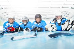 Young hockey players laying on ice rink in line royalty free stock photos