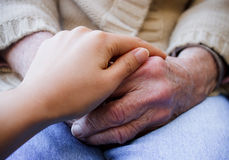 Young holding senior's hands Royalty Free Stock Photo