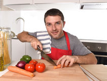 Young home cook man in apron slicing carrot with kitchen knife happy and relaxed Stock Photos