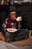 Young homeless boy eating on the street Royalty Free Stock Image