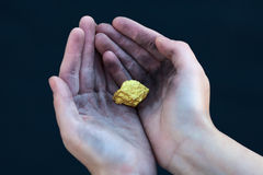 Young homeless boy holds big gold nugget Royalty Free Stock Images