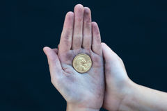 Young homeless boy holds one dollar coin Royalty Free Stock Images