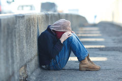 Young homeless boy sleeping on the bridge Royalty Free Stock Photos