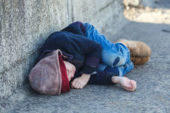 Young homeless boy sleeping on the bridge Stock Photography