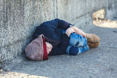 Young homeless boy sleeping on the bridge Royalty Free Stock Photo