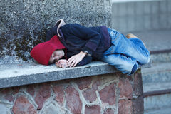 Young homeless boy sleeping on the street Royalty Free Stock Images