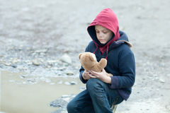 Young homeless boy on the street with bear. The young homeless boy on the street with bear Stock Photos