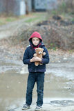 Young homeless boy on the street with bear. The young homeless boy on the street with bear Royalty Free Stock Image