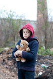 Young homeless boy on the street with bear Stock Images