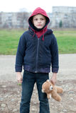 Young homeless boy on the street with bear Stock Photo