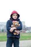 Young homeless boy on the street with bear Royalty Free Stock Photo