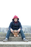 Young homeless boy on the street with bear. The young homeless boy on the street with bear Stock Photo